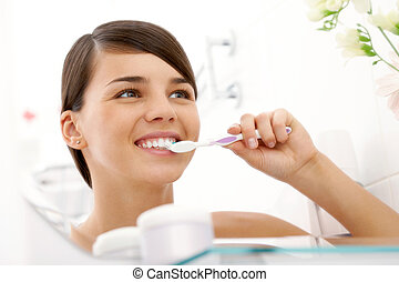 Dental care - Image of pretty female brushing her teeth in...