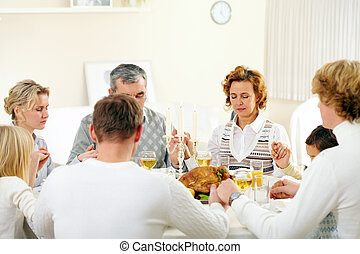 Giving thanks to God - Portrait of big family sitting at...