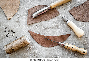Leather crafting tools on grey stone background top view