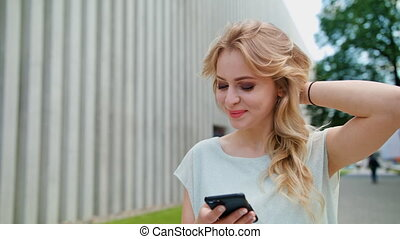 A Beautiful Young Lady Using a Mobile Phone Outdoors