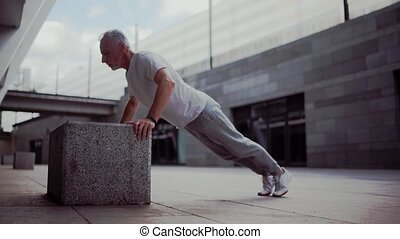 Senior man doing push ups outdoors - Train your muscles....