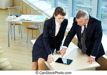 Meeting - Boss pointing at ipad screen during explanation of...