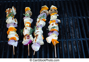 Chicken kebabs cooking on an outdoor grill