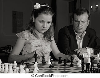 Teenage girl 12-13 years old playing on chess training with...