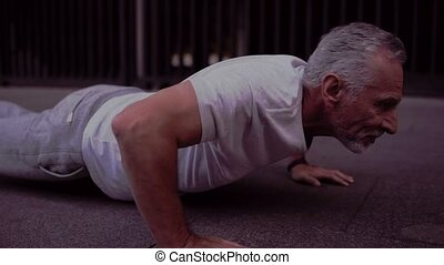 Strong senior man doing press up exercises - Full press up....