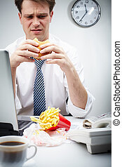Untasty hamburger - Portrait of disgusted businessman eating...