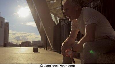 Senior sporty man resting after jogging