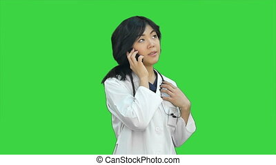 Pensive asian woman doctor using smart phone on a Green Screen, Chroma Key