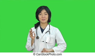 Doctor woman looking at box of pills on a Green Screen,...