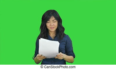 Confident asian businesswoman tearing the paper into small pieces and throwing it on a Green Screen, Chroma Key