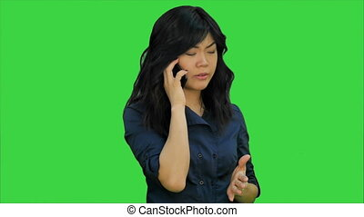 Businesswoman in blue suit talking on the cell phone on a Green Screen, Chroma Key