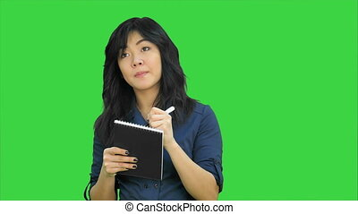 Cheerful attractive asian girl listening and writing down notes on a Green Screen, Chroma Key