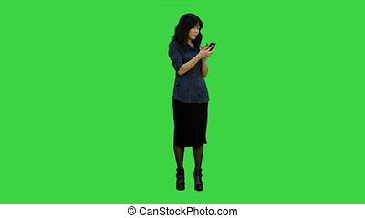 Beautiful asian girl with smartphone singing and dancing while listening to music on a Green Screen, Chroma Key