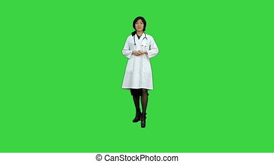 Female doctor holding up a bottle of tablets on a Green...