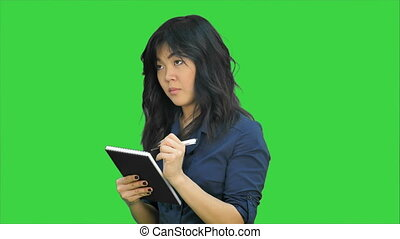 Pensive asian woman makes some notes in notepad on a Green...