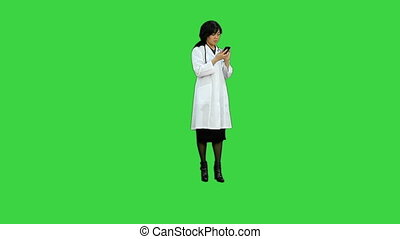 Female asian doctor with stethoscope looking at x-ray on a Green Screen, Chroma Key