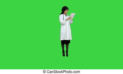 Surgeon woman doctor smile using tablet pc and talking to a camera on a Green Screen, Chroma Key