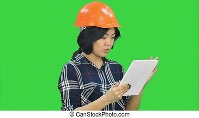 Asian engineer woman using tablet on a Green Screen, Chroma Key