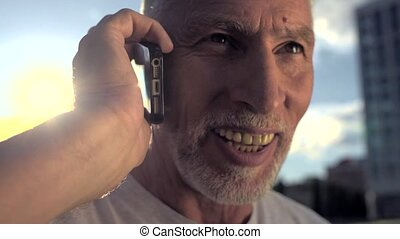 Close up of aged smiling man talking on phone