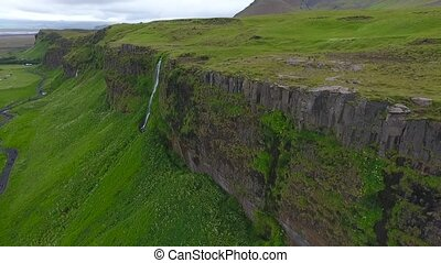 An unrealistically beautiful waterfall on a rock in Iceland....
