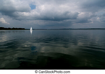 Cloudy day on lake with white boat