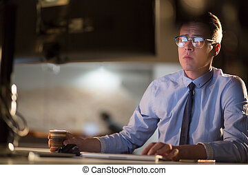 Tired businessman working late doing overtime in office at...
