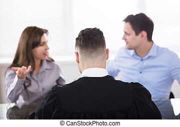 Couple Quarreling In Front Of Judge - Rear View Of A Male...