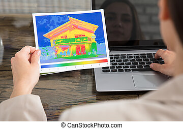 The Person Detecting Heat Loss Of A House Using Laptop -...