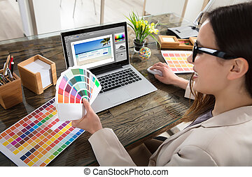 Designer Holding Colour Swatches In Her Hand - A Female...