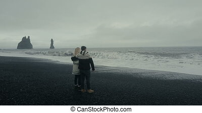 Aerial view of young couple standing on the black volcanic...