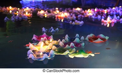 flower-shaped candle burning in the spirit pool of chinese temple
