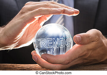 Businessman Covering Crystal Ball With Trends Text And Graphs