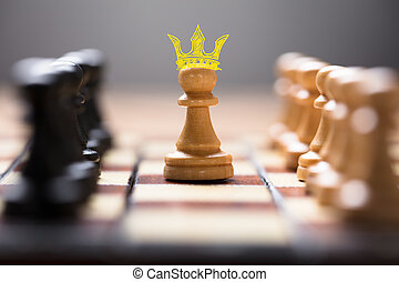 Pawn With King Crown Amidst Chess Pieces - Closeup of pawn...