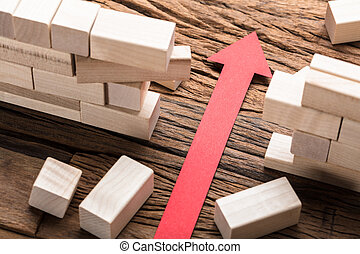 Red Paper Arrow Amidst Blocks On Wooden Table - High angle...