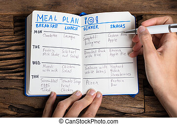 Person's Hand Filling Meal Plan On Notebook