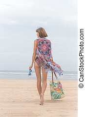 Woman tourist walking on a tropical summer vacation beach wearing sunglasses and beach bag relaxing on travel holidays. Young lady in luxury fashion beachwear, Bali island, Indonesia.