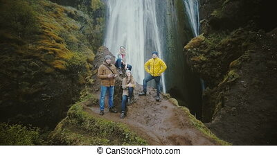 Aerial view of the tourists in Gljufrabui waterfall in Iceland. Copter moving away from friends, selfie on drone.