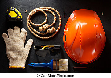 hardhat and tools  on black background