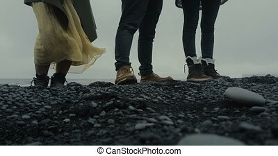 Close-up view of people foot standing on the black volcanic...