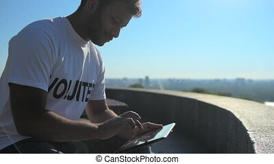 Positive male volunteer using his tablet outdoors - Advanced...