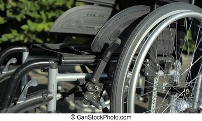 Pleasant man pushing a wheelchair - Necessary equipment....