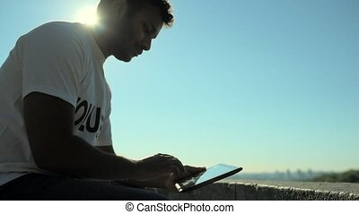 Low angle of a concentrated volunteer using the tablet -...