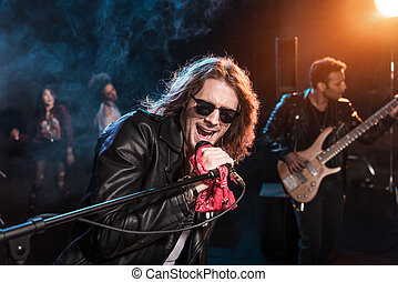 Male singer with microphone and rock and roll band performing hard rock music on stage