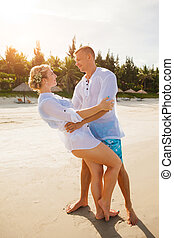 Happy couple hugging on the beach