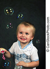 Soap bubbles - The small boy with soap bubbles in studio