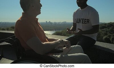 Positive helpful volunteer talking with a wheelchaired man -...