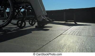Low angle of a helpful man pushing a wheelchaired person -...