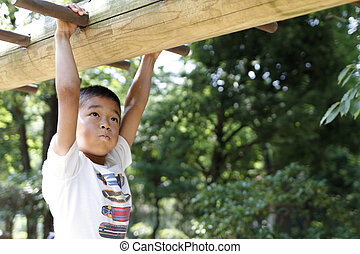 Japanese boy playing with a monkey bars (second grade at...