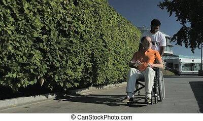 Positive hindu volunteer walking with a wheelchaired man