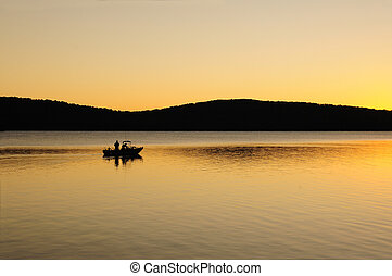 Early morning fishing boat on a lake at dawn - Silohuette of...